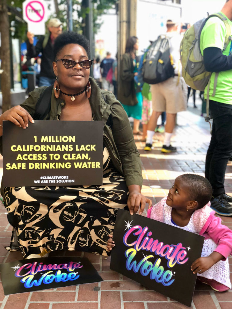 "A mother and her small child are holding up Climate Woke signs that say: ""1 million Californians lack access to clean, safe drinking water"""